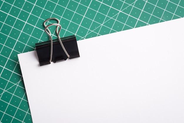 Черная скрепка на белой бумаге