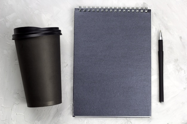 Black paper cup of coffee to go black notebook and pen