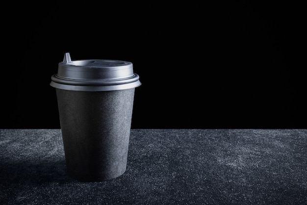 Black paper disposable takeout drink cup on dark surface and black background.