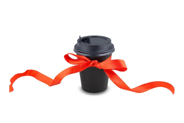 Black paper disposable takeout drink cup with bow made of gift long red ribbon. isolated on white background. coffee as a present