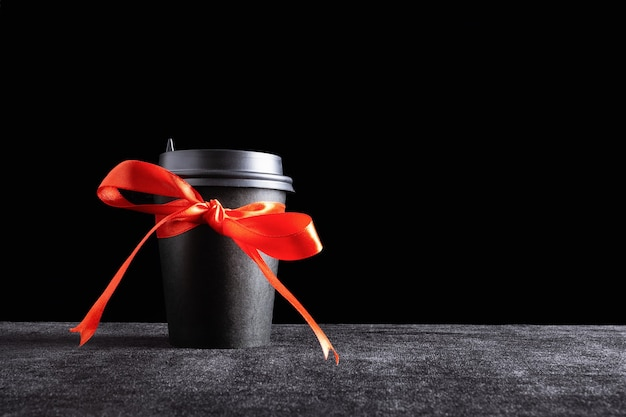 Black paper disposable takeout drink cup with bow made of gift red ribbon on dark surface and black background.
