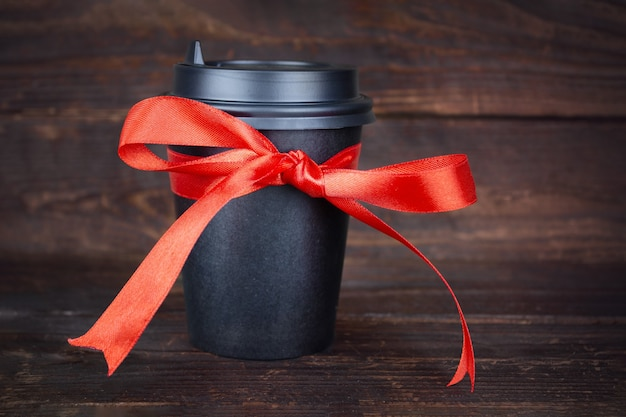 Black paper disposable takeout drink cup with bow made of gift red ribbon on wooden plank background. coffee or tea as a gift