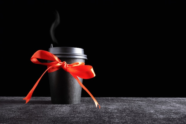 Black paper disposable takeout drink cup with steam over the lid with bow made of gift red ribbon on dark surface and black background