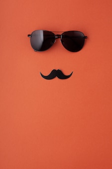 Black paper moustaches with glasses with copy space. men's health awareness month, masculinity, fathers day concept