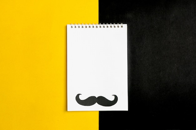 Black paper mustache, hat, glasses , notepad on yellow background month donations, fathers day concept