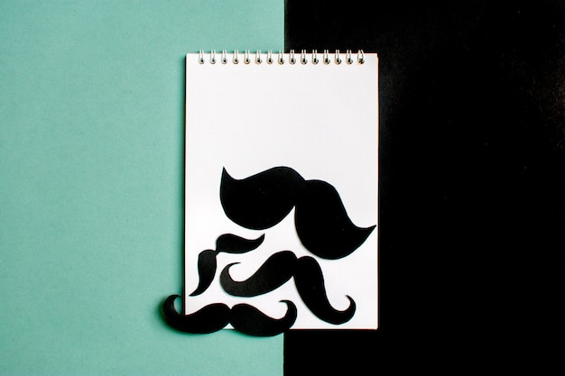 Black paper mustache, notepad on blue background month donations control of prostate cance