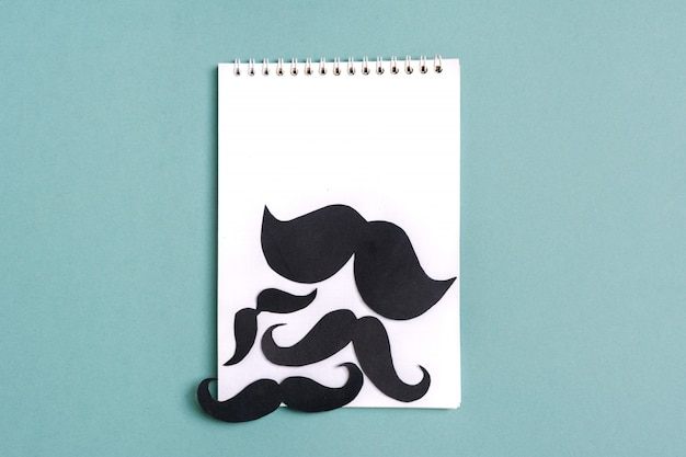 Черная бумага усы, блокнот на синем фоне месяц пожертвований, концепция день отцов