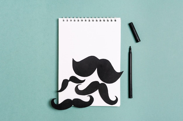 Black paper mustache, notepad, pencil on blue background month donations control of prosta