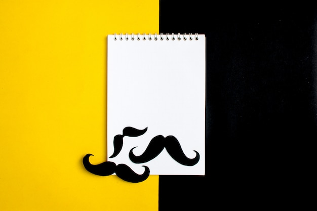 Black paper mustache, notepad, pencil, yellow background month donations control of prosta