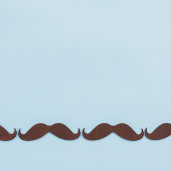 Black paper mustaches in row