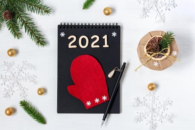 Черный бумажный блокнот для рождественского списка желаний с красной варежкой на белом столе рядом с упакованным подарком