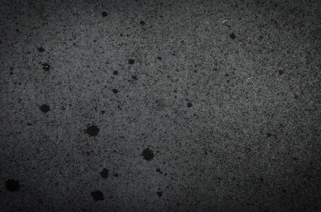 Black paper texture background with scuffs, scratches, stains.