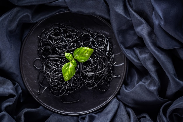 Black pasta and basil on a dark background. black spaghetti with cuttlefish ink on a black cloth. pasta with fresh basil on a black plate. copy space. top view