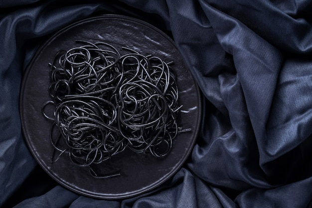Black pasta on a black plate. squid ink black pasta on a dark background. black spaghetti with cuttlefish ink. copy space. top view