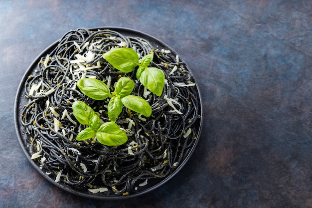 Black pasta with grated cheese and basil on a dark background. black spaghetti with cuttlefish ink on black plate. pasta with parmesan cheese and fresh basil. copy space. top view