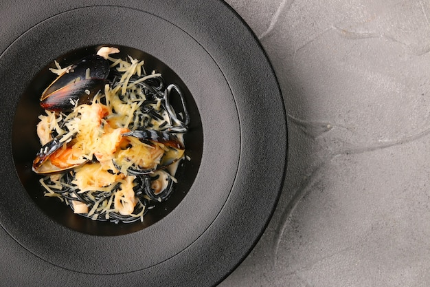 Black pasta with mussels and cheese top view.