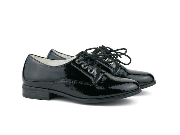 흰색 표면에 묶인 끈 izolirovannye와 블랙 페이턴트 가죽 신발. 유행 학교 신발.