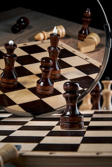 The black pawn looks in the mirror and sees the reflection of the king and queen, the concept of strategy, planning and decision-making, the concept of a leader for success