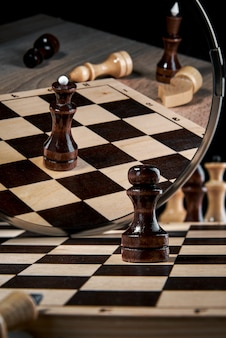 The black pawn looks in the mirror and sees the reflection of the queen, the concept of strategy, planning and decision-making, the concept of a leader for success
