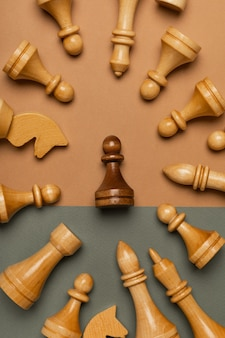 Black pawn surrounded by white chess pieces on flat background