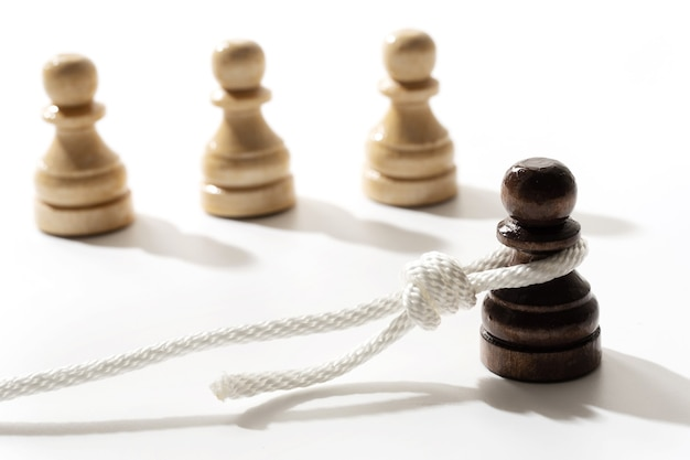 Black pawn with a hangman's loop on a neck. concept of racism and discrimination.
