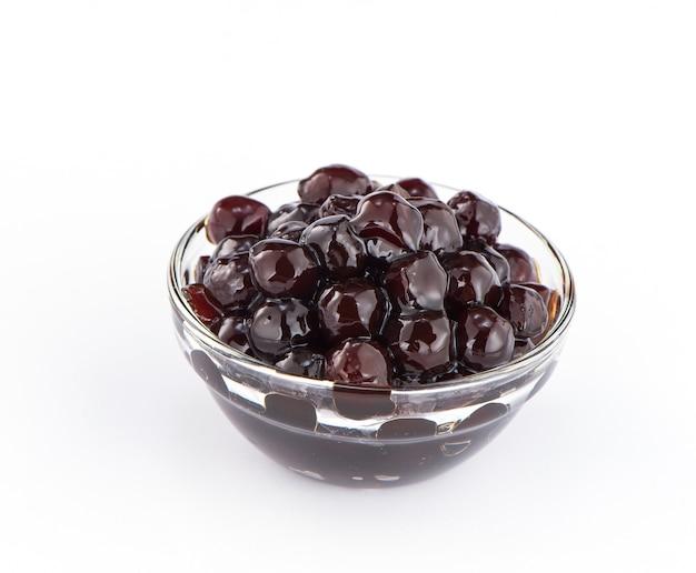 ブラックパール。白い背景の上のバブルティーのためのゆでたタピオカ真珠。コピースペース