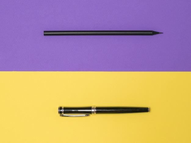 노란색과 보라색 배경에 검은 색 펜과 검은 색 연필. 세련된 문구.