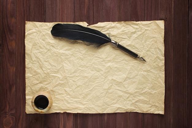 나무 탁자에 있는 오래된 종이 배경에 검정 펜과 잉크 프리미엄 사진