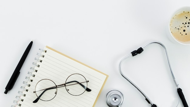 Black pen; eyeglasses on spiral notepad; stethoscope and coffee cup on white backdrop