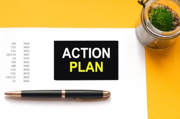 A black pen, a green plant in a glass jar, and a black card on a white sheet of paper on yellow background. text: action plan, white and yellow letters. financial and motivation concept.