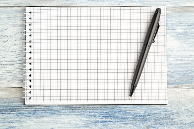 Black pen and paper notebook with space for text on a light blue old wooden background.