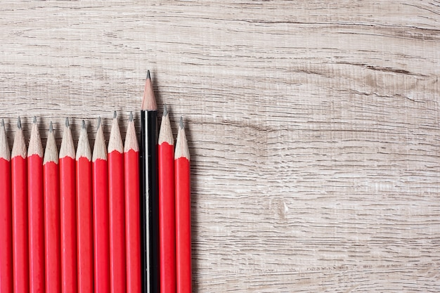 Black pencil different from crowd of red pencils