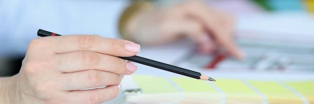 カラーパレットのインテリアデザインスタジオのコンセプトを手に黒鉛筆