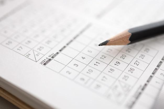 Black pencil lies on calendar with dates