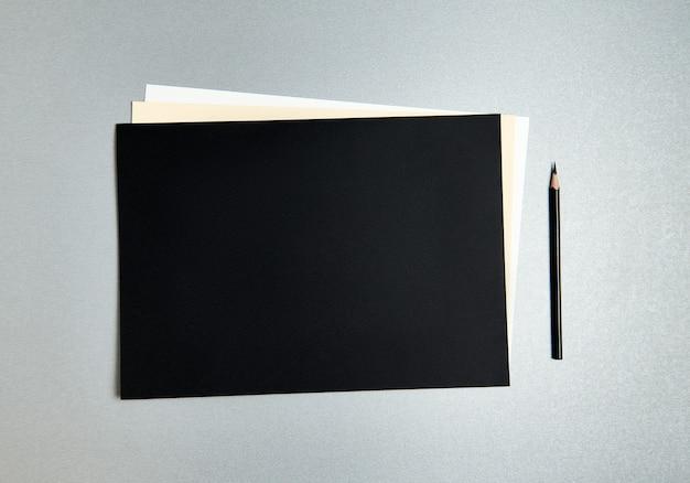 Черный карандаш рядом с дизайнерской бумагой разных цветов на сером фоне. плоская планировка. вид сверху