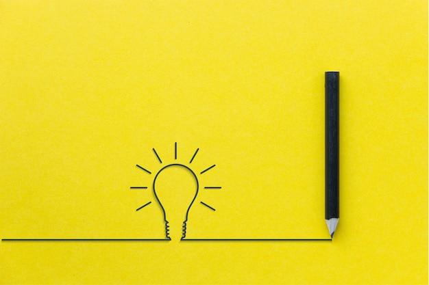 Черный карандаш на желтом backgroud с лампочкой