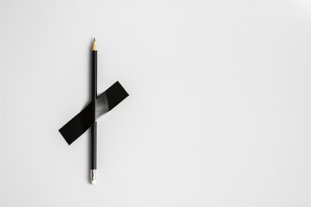 Black pencil pinned with black cloth tape.