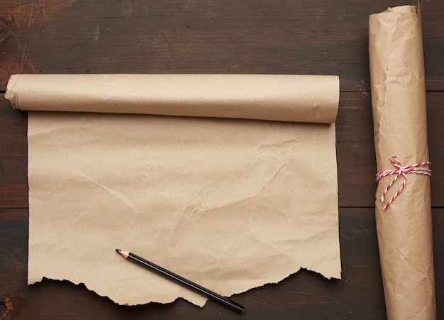 Black pencil and roll of untwisted brown paper on a wooden surface from old boards