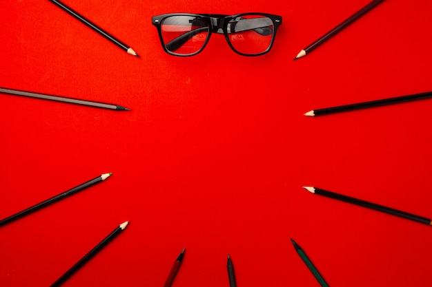 Black pencils and glasses on red background top view, copy space