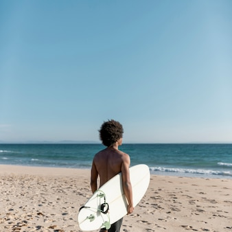 Black pensive man with surfboard looking away