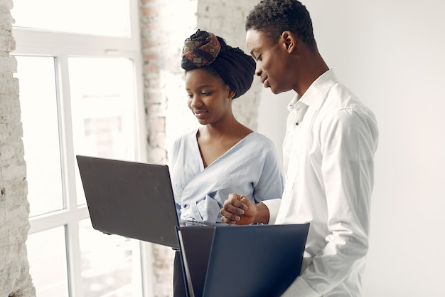 Black people standing on a white wall with a laptop