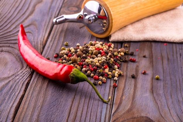 黒胡椒のとうもろこし、赤唐辛子、黒胡椒の粉を木製のテーブルに