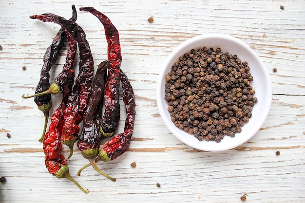 Black peppercorns on small white plate on white wooden table with dried black chili peppers, top view, spices