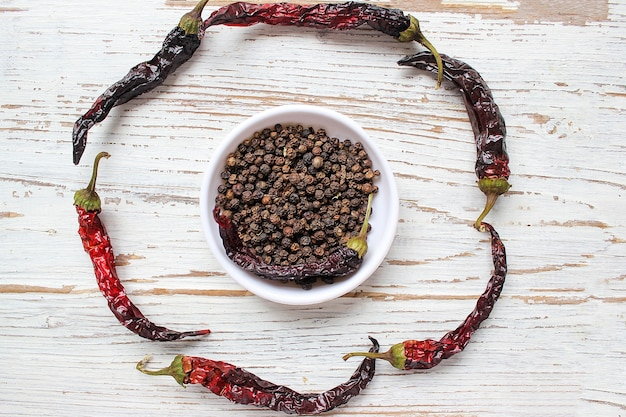 Black peppercorns on small white plate on white wooden table with dried black chili peppers, top view,