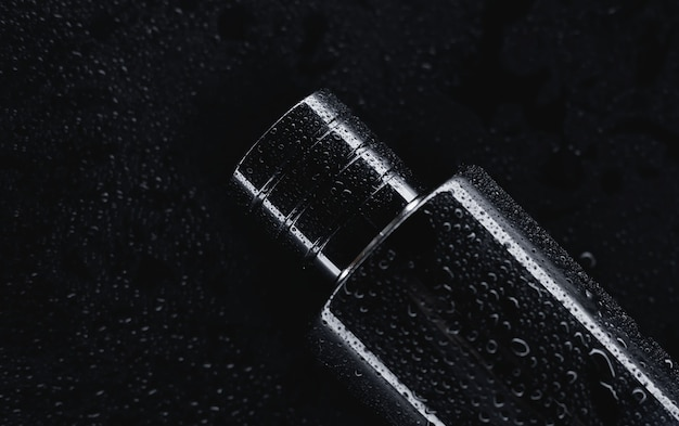 Black perfume on a dark background close up