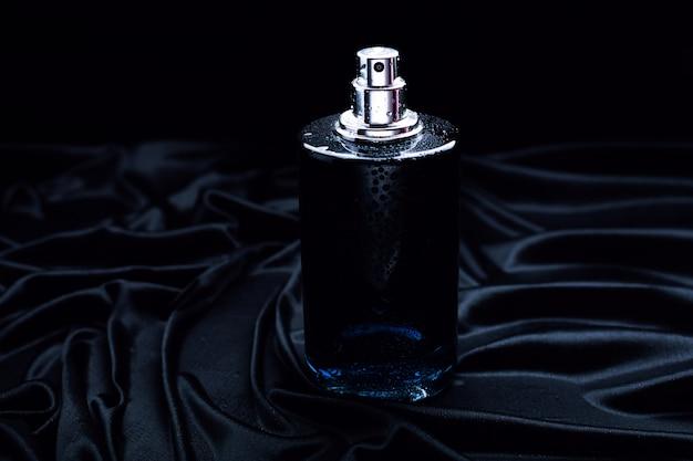 黒い布の背景に黒い香水
