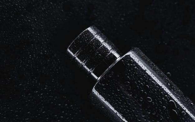 暗い背景に黒い香水をクローズアップ