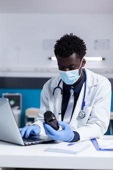 Черный человек с профессией медика, используя ноутбук