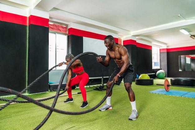 フィットネスジムでクロスフィットバトルロープのエクササイズを行うためにボディービルの女性を指導する黒人のパーソナルトレーナー。トレーニングトレーニングコーチのビジネスコンセプト