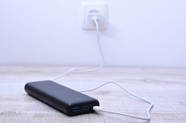Black phone power bank plugged in the socket on the wall for charging on wooden table